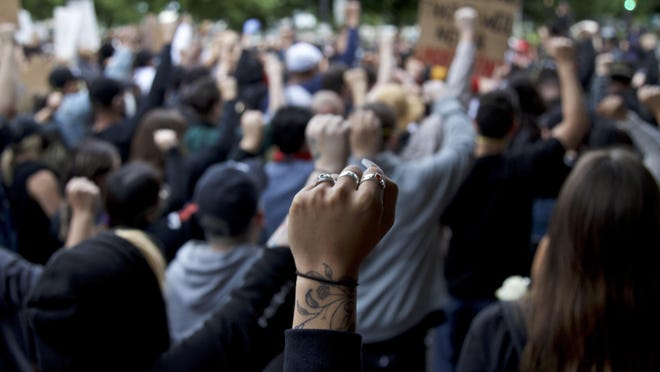 A demonstrator holds up a fist in Portland during a protest against police brutality and racism sparked by the death of George Floyd, who died May 25 after being restrained by police in Minneapolis.