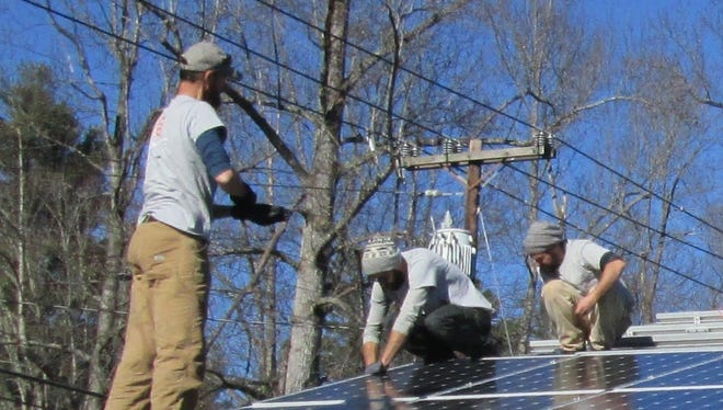 The crew from Sugar Hollow Solar installs solar panels Thursday on the roof of First Congregational United Church of Christ in Laurel Park.