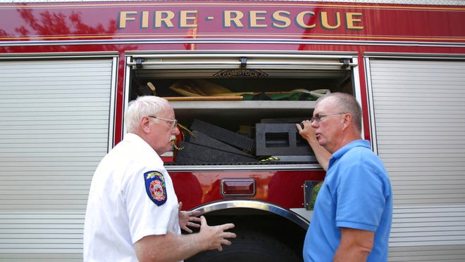 In this June 21, 2013, photo, Comstock Fire Chief Wally Culver, left, trains his replacement, Edward Switalski, at the Comstock Fire Department east station in Comstock Township, Mich.  Switalski has died after he was struck by an out-of-control vehicle as he responded to another crash on Interstate 94 in southwestern Michigan, authorities said Thursday, June 15, 2017.