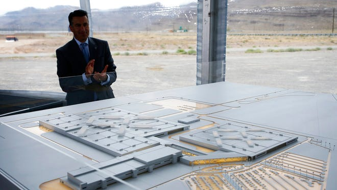 In this April 13, 2016 file photo, Nevada Gov. Brian Sandoval looks at a model for a Faraday Future factory in North Las Vegas, Nev. Electric car maker Faraday Future said Monday, July 10, 2017 that it is deserting its plan to construct a $1 billion manufacturing plant in southern Nevada eight months after suspending the project and sinking at least $120 million into it.