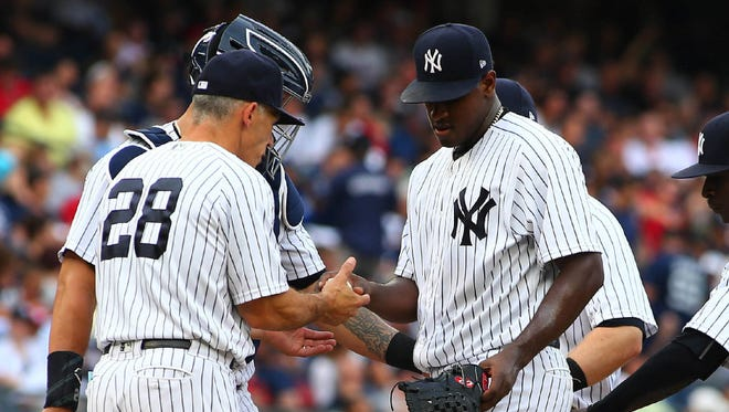 Yankees starter Luis Severino hands the ball to manager Joe Girardi as he's taken out of the game in the fifth inning on Saturday at Yankee Stadium. Severino struggled against the Red Sox, allowing 10 runs (eight earned) in just 4.1 innings.