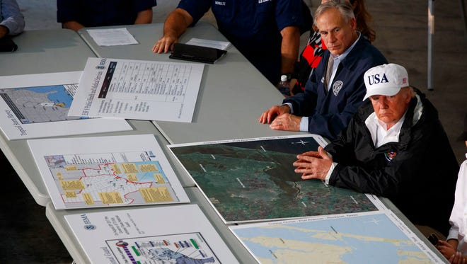 Texas Gov. Greg Abbot and President Donald Trump listen during a briefing on Harvey relief efforts, Tuesday, Aug. 29, 2017, in Corpus Christi, Texas. (AP Photo/Evan Vucci)
