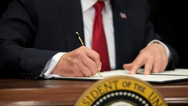President Trump signs an executive order on Oct. 12, 2017.