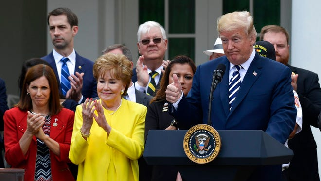 President Donald Trump speaks before signing the VA Mission Act of 2018 during a ceremony in the Rose Garden of the White House in Washington June 6, 2018. The bill will expand private care for veterans as an alternative to the troubled Veterans Affairs health system. Standing with Trump are Rep. Martha McSally (left), R-Ariz., and former Sen. Elizabeth Dole of North Carolina.