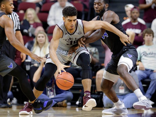FILE - In this Thursday, Dec. 21, 2017, file photo, Texas A&M center Tyler Davis (34) tries to drive between Buffalo guard CJ Massinburg (5) and forward Ikenna Smart (34) during the second half of an NCAA college basketball game in College Station, Texas. Improved balance has created the possibility of a more unpredictable race for the title as the Southeastern Conference gets ready to begin league competition. (AP Photo/Michael Wyke, File)