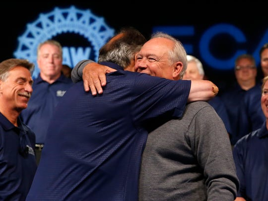 Fiat Chrysler Automobiles CEO Sergio Marchionne, left, and United Auto Workers President Dennis Williams hug during a ceremony to mark the opening of contract negotiations Tuesday, July 14, 2015 in Detroit.
