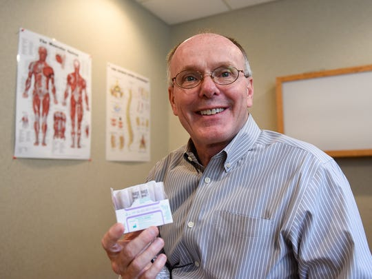 Jeff Varner holds a box of acupuncture needles Saturday, June 18, at Crossroads Chiropractic Clinic.