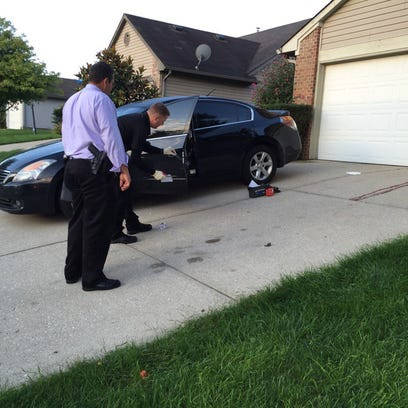 A detective and evidence technician examine a car that