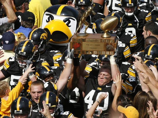 Iowa's Mike Klinkenborg (40) raises the Cy-Hawk Trophy high in the air in celebration of the Hawkeyes' 27-17 win Sept. 16, 2006, at Kinnick Stadium in Iowa City.