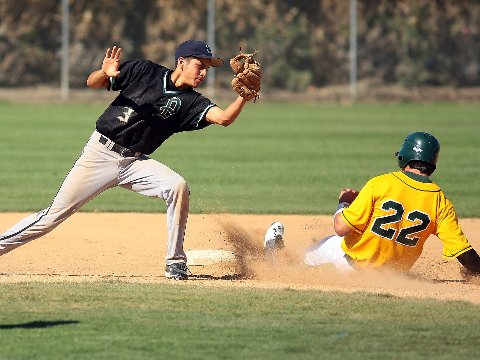 Perris High School's Jorge Medina (3, left) reaches down to try to tag Notre Dame's Danny Baytosh (22, right) out at second base on Monday afternoon, March 30, 2015 during a game at Coachella Valley High School in Thermal, Calif. The schools are playing this week in the annual Coachella Valley Rotary baseball tournament. Baytosh was safe, but was left on base at the end of the inning.