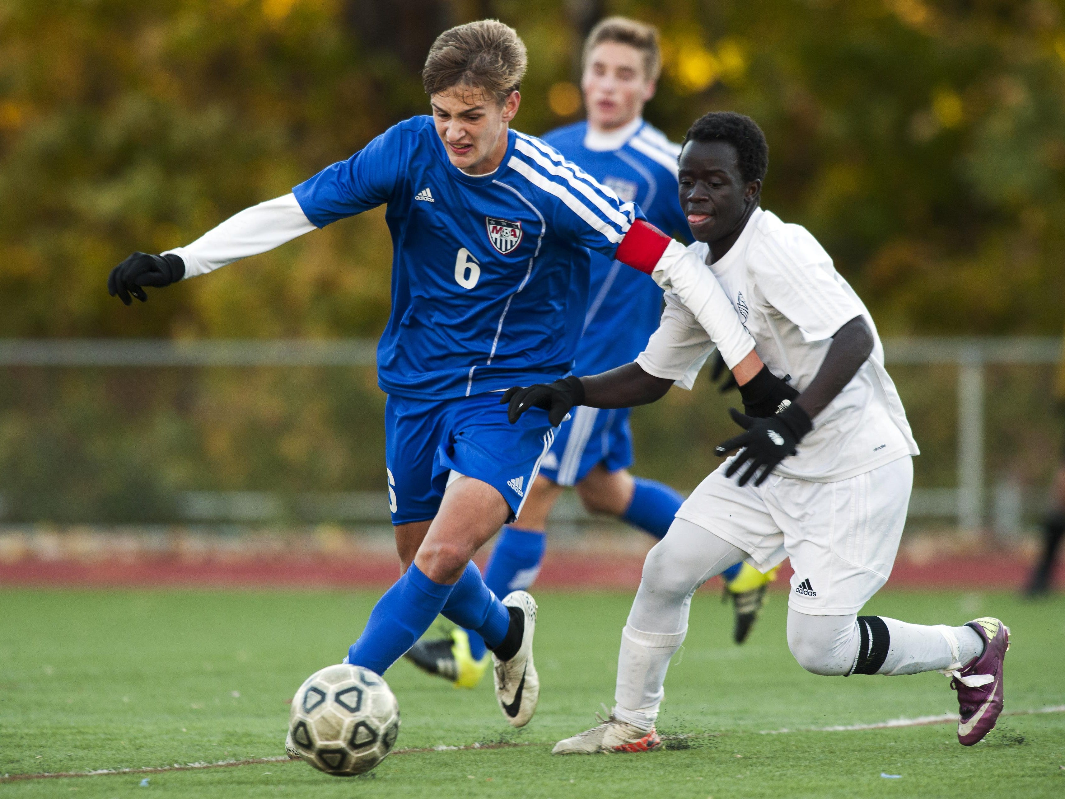 Mount Anthony's Jack Peterson (6) gets past Burlington's Maenda Bienfait Badibang (21) with the ball during the quarterfinal boys soccer game between Mount Anthony and Burlington at Buck Hard Field on Friday afternoon October 23, 2015 in Burlington.