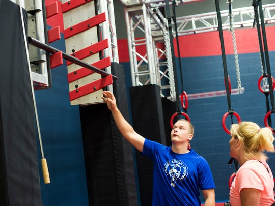 "Wendy Oberholtzer, right, receives instruction from Thomas Alquist, a course instructor at Paramount Sports Complex in South Londonderry Township, on how to do the salmon ladder as she trains for ""American Ninja Warrior"" on Tuesday, June 7, 2016."