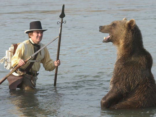 Adam, a 450-pound grizzly bear, is coaxed into a fierce display as actor Norman Anderson portrays Meriwether Lewis while filming a scene in the Missouri River in Great Falls in 2004. The re-enactment was part of a film highlighting the Lewis and Clark expedition's portage around the Great Falls of the Missouri, when one grizzly chased Lewis into the Missouri River.  Now grizzlies are returning to the Great Falls area after a long absence.