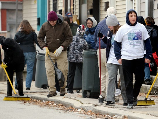 "Volunteers work the ""Duke Street Clean Sweep"" during"