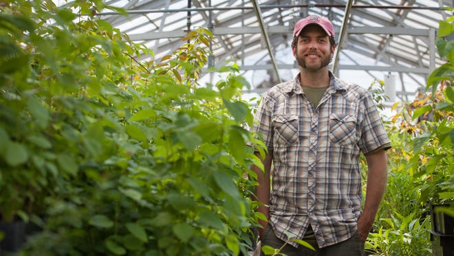 Seth McDonough, the new manager of sustainable agriculture at Duke Farms, is photographed next to plants that are destined for a permaculture garden.