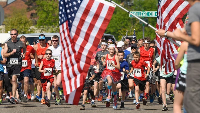 Runners come off the starting line during the Old Glory Run on Saturday, May 21, 2016, in St. Joseph. About 1,000 runners participated the annual 5K run.