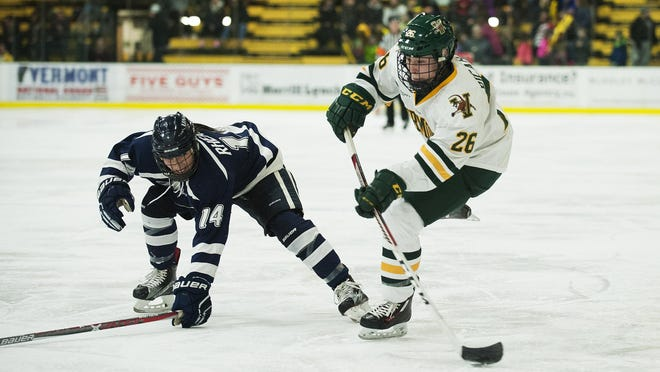 Vermont's Eve-Audrey Picard (26) shoots the puck past New Hampshire's Jenna Rheault (14) during the women's hockey game between the New Hampshire Wildcats and the Vermont Catamounts at Gutterson Field House on Friday night February 3, 2017 in Burlington. (BRIAN JENKINS/for the FREE PRESS)
