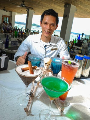 Bartender Jun Navarro serves up chillin' cocktails to welcome restless Halloween spirits to the Tasi Grill at the Dusit Thani Guam Resort in Tumon on Oct. 26. Clockwise in the foreground, Witches' Glare, Haller's Web and Donnauro's Spell.