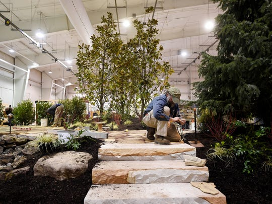 Landscape foreman Joel Bergstrom hooks up the lights  for the Hively Landscapes exhibit at the show, which offers home and garden displays, project ideas and also a Kids' zone to keep young attendees occuped.