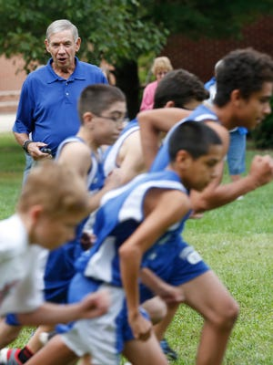 Frankfort Middle School cross country coach Mike Poehlein cheers on his runners at the start of the boys race against Rossville Monday, October 3, 2016, in Rossville. Poehlein, 76, was Purdue's track and cross country coach for more than three decades.