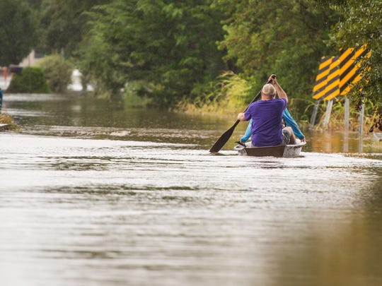 Jeremy and Chelsea LeMieux paddle pirogue through flood waters as record rainfall causes flooding across south Louisiana.