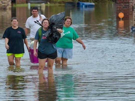 People wade in water near flood damaged homes in Highland Ridge Subdivision in Youngsville, Sunday. Torrential rains swamped parts of southern Louisiana, causing widespread flooding.