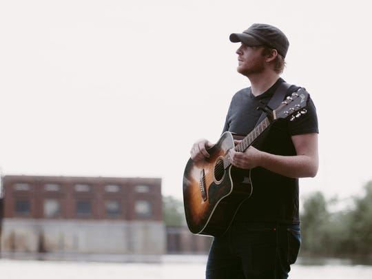 Little Falls-based singer-songwriter Michael Shynes poses with his guitar.