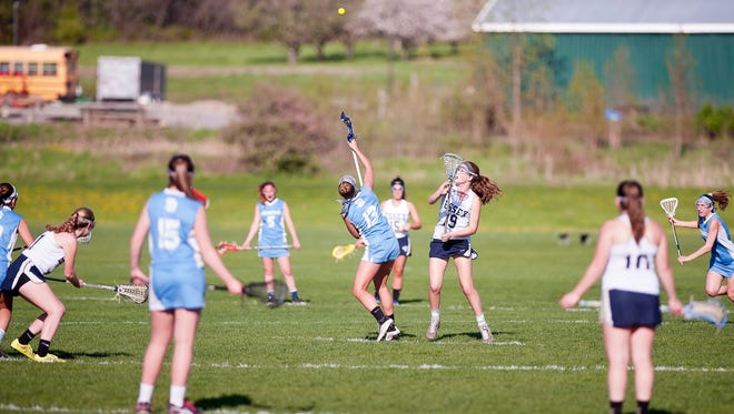 South Burlington's Annika Nielsen (13) and Essex's Olivia Miller-Johnson vy for control of the draw during Tuesday's high school girls lacrosse game in Essex.