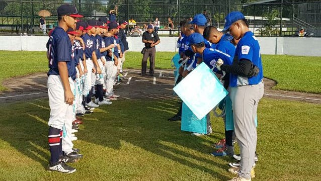 Team Guam, left, and the team from the Commonwealth of the Marianas, meet before the start of their game in the Asia-Pacific Regional Championships July 1 in the Philippines.