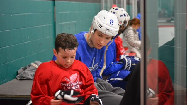 Salem senior forward Richie Corso encourages this young, budding player during a breather.