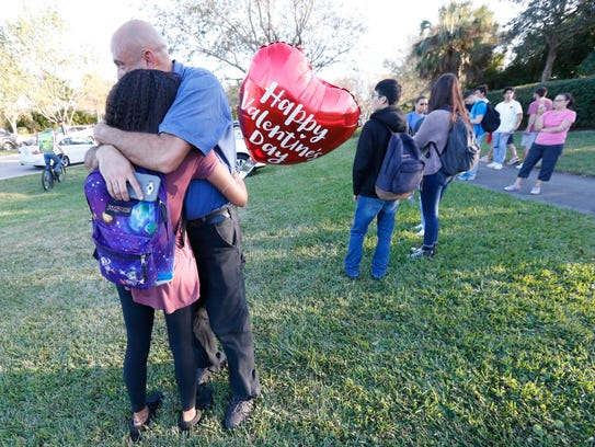 Family members embrace following the Feb. 14 shooting