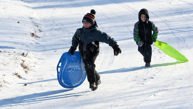 Caleb Gahagan and Joseph Gahagan race back up the hill for another slide in Kingsgate Subdivision in Farragut on Saturday, Jan. 7, 2017.