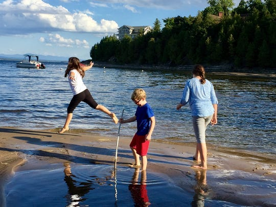 Sarah Shamus leaps on the sand as she frolicks in Lake Champlain with her brother, Sam, and sister, Julia in September 2016. It was part of a family trip to Plattsburgh, N.Y.