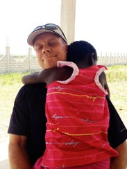 Scott Hamilton hugs Evelyne in Haiti shortly before