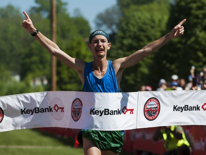 Tyler Andrews crosses the finish line in the lead during the 26th Annual KeyBank Vermont City Marathon on Sunday May 25, 2014, in Burlington.