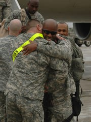 Sgt. 1st Class Derrick Jerry is greeted by a friend Monday upon his return from Iraq with fellow members of the 4th Brigade Combat Team, 10th Mountain Division. England Airpark, a former Air Force base, has maintained a strong connection with the military through nearby Fort Polk.