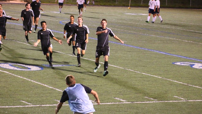 The Owen Warhorses celebrate after scoring the tying goal against T.C. Roberson in double overtime.