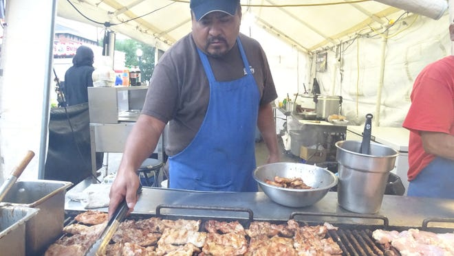 Carlos Arenas of Smithville flips a few pieces of bourbon chicken inside the Louisiana Grill booth at the 2016 Galion Oktoberfest.