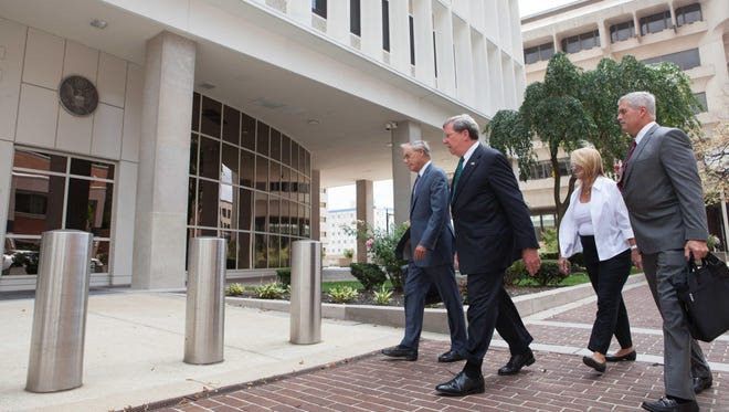 Former Wilmington Trust President Robert Harra Jr. (second from left) arrives at the federal courthouse in Wilmington on Aug. 16 for his arraignment.