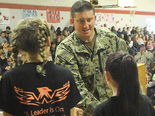 Veteran Scott Burleigh shakes hands with students during the assembly.