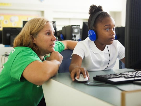 Denise Sterne watches as her second grade student Jade Allen reviews math problems in the computer lab during an intersession half-day at Bass Elementary in Lynchburg on Sept. 3, 2015.