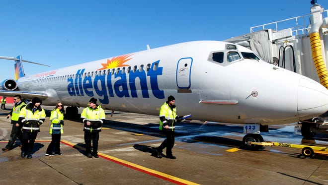 Ground crew members disperse after preparing an Allegiant  MD 82 jet for departure from Cincinnati/Northern Kentucky International Airport in February 2012. The company just announced it will start a route from CVG to the New York City market in November.