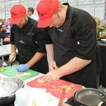 La Vita Bistro Executive Chef Eirik Kauserud, right, prepares large shrimp to accompany his dish during the Livingston County Iron Chef competition. He won this year's Iron Chef title and will be the main judge during the Iron Chef Kids Cooking Challenge on Wednesday night.