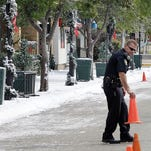 Against a backdrop of fake snow, Wyoming Police officer Donald Campbell places traffic cones in the 400 block of Wyoming Avenue where Mariah Carey is directing a Christmas-themed movie.