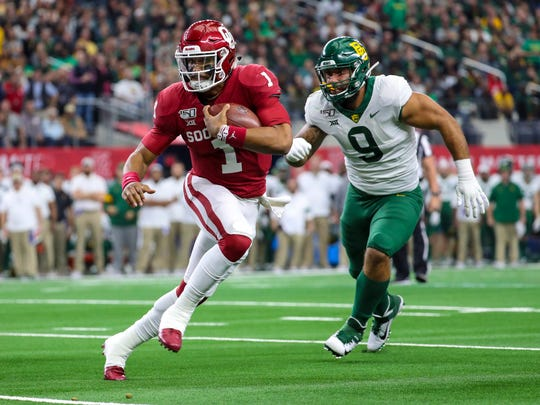 Dec 7, 2019; Arlington, TX, USA; Oklahoma Sooners quarterback Jalen Hurts (1) runs past Baylor Bears defensive end James Lockhart (9) during the first quarter in the 2019 Big 12 Championship Game at AT&T Stadium. Mandatory Credit: Kevin Jairaj-USA TODAY Sports