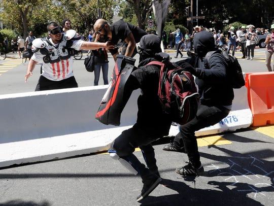 Demonstrator Joey Gibson, second from left, is chased