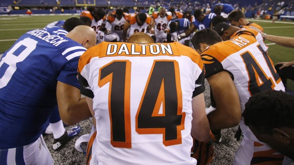 Cincinnati Bengals quarterback Andy Dalton (14) kneels down in a joint prayer circle after the preseason NFL game between the Cincinnati Bengals and Indianapolis Colts, Thursday, Sept. 3, 2015, Lucas Oil Stadium in Indianapolis.