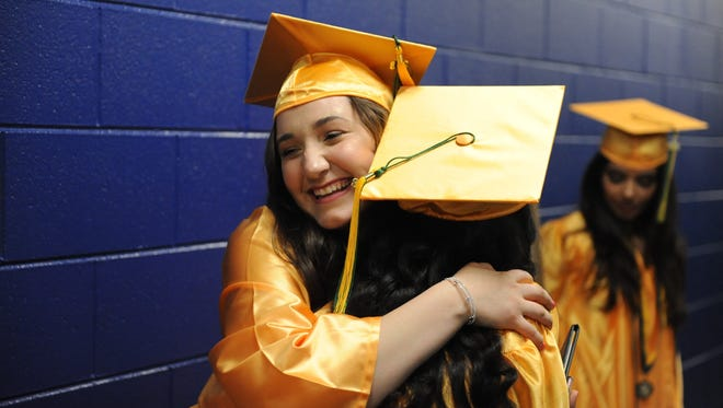 Harrison High School graduates Aneeta Eeso (left) and Nadine Hikmat exchange congratulatory hugs June 10 at USA Hockey Arena.