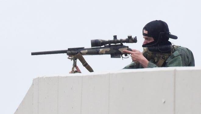 A sniper on top of a parking garage waits at the ready during the standoff. Sioux Falls law enforcement including a SWAT team surrounded the public library in downtown on Monday Sept. 25, 2017 when responding to a parolee who was possibly armed. The standoff ended peacefully and the parolee was taken into custody.