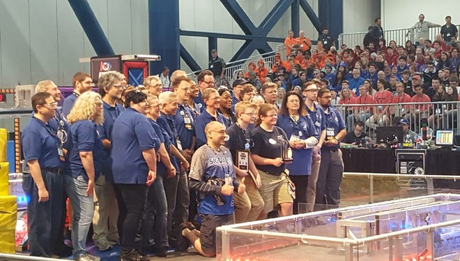 Bomb Squad members Matthew Rhodes front middle left, and Sophia Meinshuasen, front middle right, pose for a photo after the Mountain Home High School robotics team won the Quality Award at the world championship this weekend.